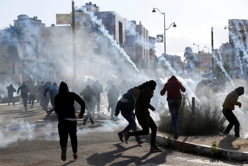 Manifestantes palestinos são alvo de bombas de gás lançadas pelas tropas de Israel perto de Ramallah, um dia após decisão de Trump de reconhecer Jerusalém como capital de Israel (Foto: REUTERS/Mohamad Torokman)